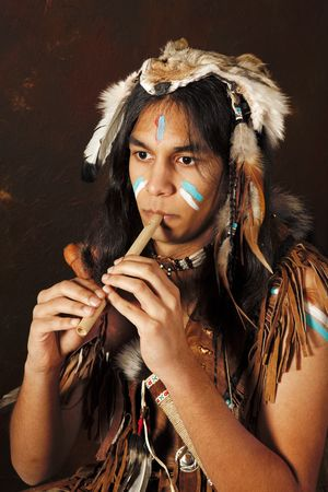 apache: Portrait of an Indian in traditional costume wearing eagle feathers, coyote fur and beads