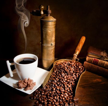 steaming coffee: Antique coffee grinder with steaming coffee, cookies and books Stock Photo