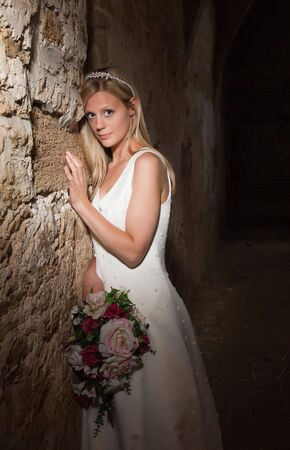 Bride in white posing against a medieval grunge barn wall Stock Photo - 6801797