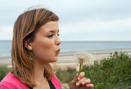 Young woman blowing away dandelion seeds on the beach Stock Photo - 6801794