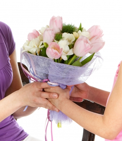 Hands of a girl giving her mother flowers photo