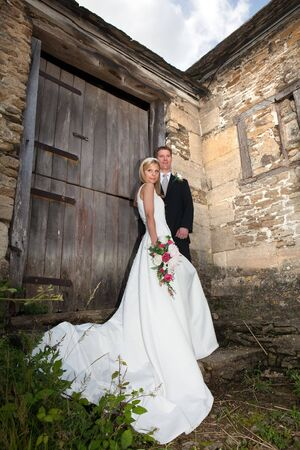 Young wedding couple against a grunge medieval wall Stock Photo - 6869748