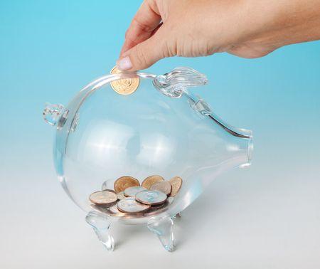 Hand adding a dollar to a glass piggy bank photo
