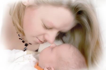 A moment of tenderness between a loving mother and her newborn baby (15 days old) photo