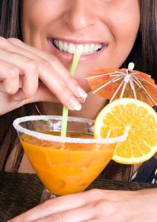 Closeup of a young woman drinking an orange cocktail Stock Photo - 6901233