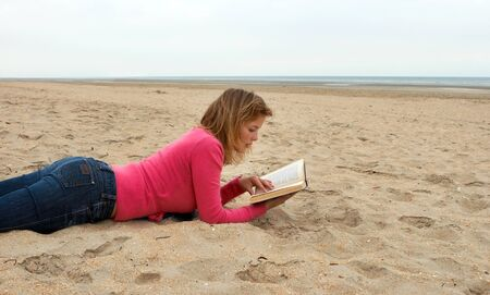 Young woman reading a book on an empty beach photo