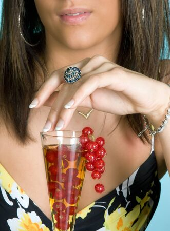 Young brunette touching a fruit cocktail with her hand photo