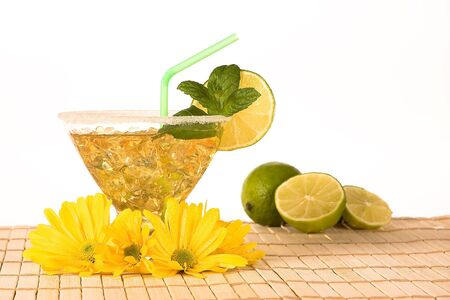 Yellow cocktail drink with lemon, straw and flowers Stock Photo - 7010315
