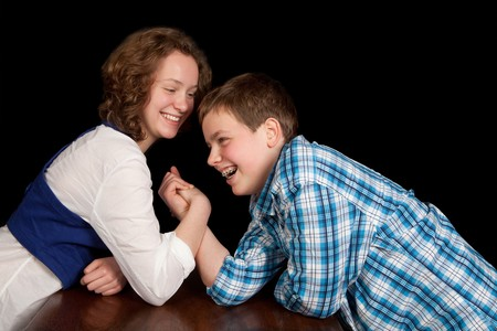 wrestle: Caucasian teenager boy and girl enjoying an arm-wrestling challenge Stock Photo