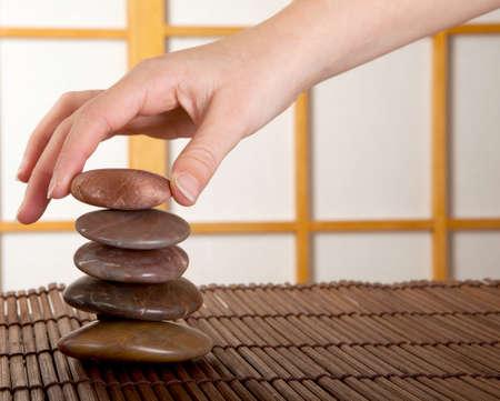 Hand stacking zen stones in a japanese interior with shoji sliding windows photo