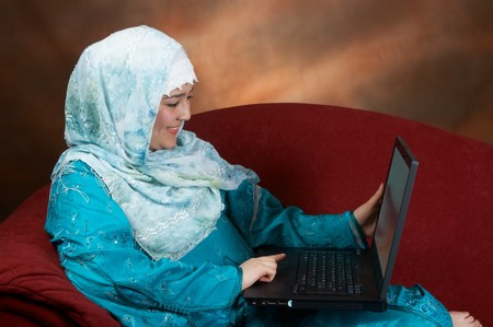 Attractive young muslim woman sitting on a sofa, enjoying her work on a laptop photo