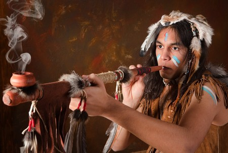 man smoking: Retrato de un indio en traje tradicional, llevando las plumas de �guila, piel de coyote y perlas