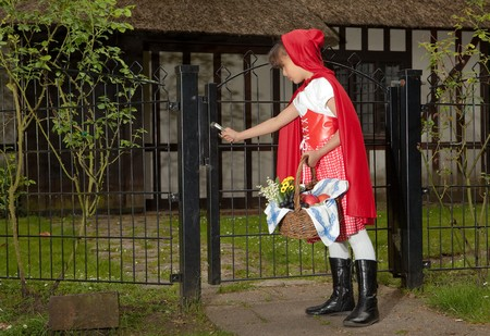 Little red riding hood opening the gate the her grandmother's cottage Stock Photo - 7075877