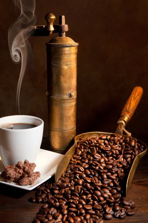 steaming: Antique coffee grinder with steaming coffee, cookies and books Stock Photo
