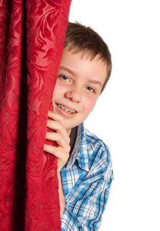 Teenager with braces peeping from behind a curtain photo
