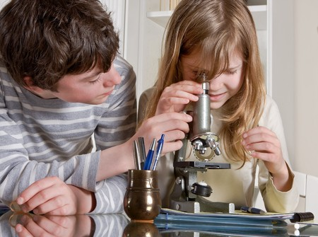 teens school: Two teenagers helping each other with a microscope Stock Photo