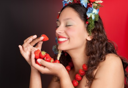 Summer woman with strawberries, fruit and flowers in her hair eating strawberries photo