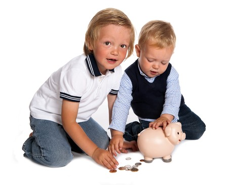 Two toddler brothers playing with money and their pink piggy bank Imagens