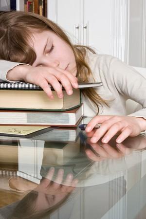 Teenager girl fallen asleep over her homework photo