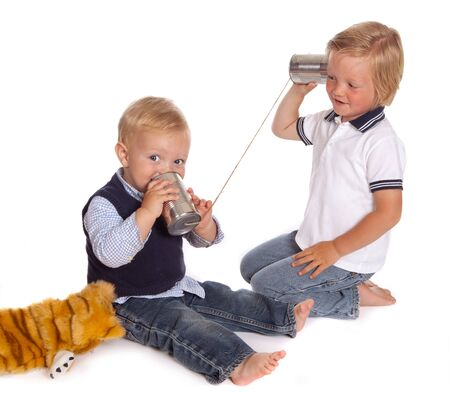 Two little brothers talking on the phone using two cans and a piece of rope Stock Photo - 7246459