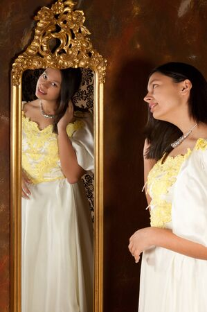Pretty woman in vintage gown looking into an antique mirror photo