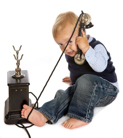 Blonde toddler boy playing with a black antique telephone photo