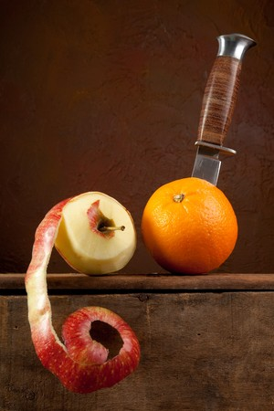 Peeled apple and a dagger cutting an orange Stock Photo - 7332774
