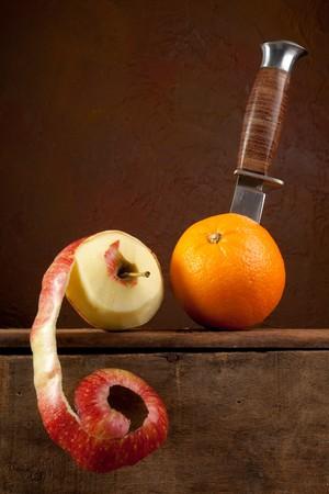 Peeled apple and a dagger cutting an orange Stock Photo - 7332774