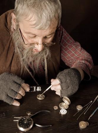 bärtiger mann: Alte b�rtigen Mann geht antike Uhren, die mit Hilfe einer Lupe  Lizenzfreie Bilder