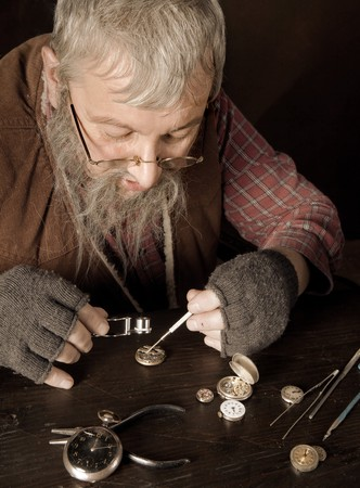 watchmaker: Old bearded man reparing antique watches using a magnifying glass Stock Photo