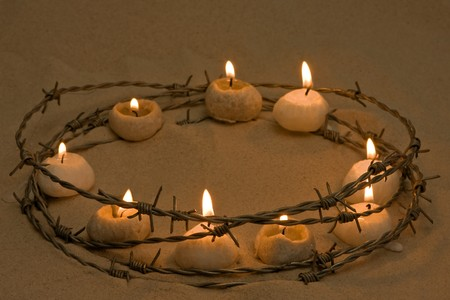 human rights: Candles in a ring of barbed wire, symbol of human rights and hope Stock Photo