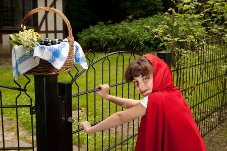 Little red riding hood arriving at the gate of her grandmother's cottage Stock Photo - 7430664
