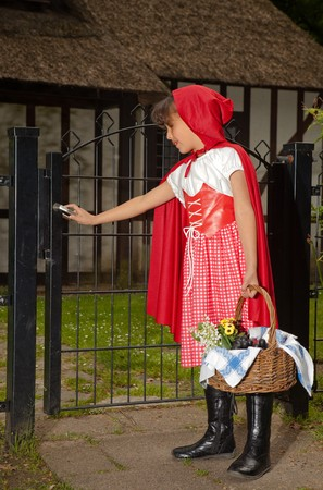 Little red riding hood opening the gate the her grandmother's cottage Stock Photo - 7481912
