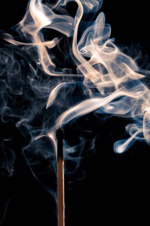 Single match stick being blown out with a wisp of smoke photo