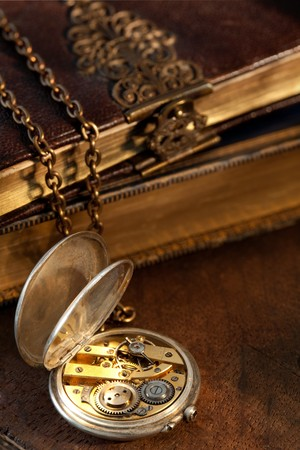 Blurred old books on the background of an antique pocket watch photo