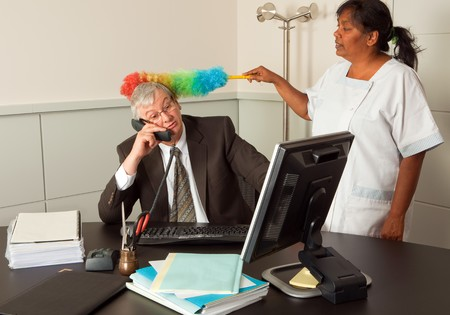 Funny cleaning woman cleaning the office of the manager including his face photo