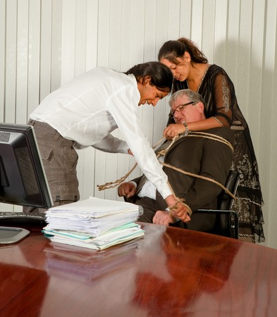 tied up: Employees tying the office manager to his chair with a rope