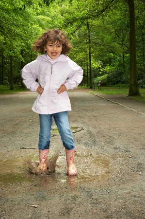 Little girl making a big splash in a water puddle photo