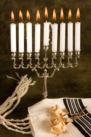 Hanukkah candle-holder and a jewish prayer shawl photo