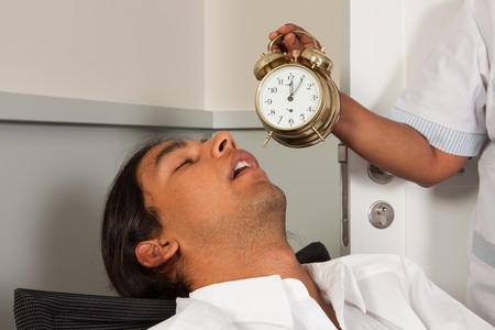 Cleaning woman holding an alarm clock next to a sleeping office worker Stock Photo - 7597764