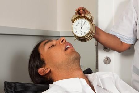 femme nettoyage: Femme de m�nage, tenant un r�veil � un employ� de bureau endormi Banque d'images