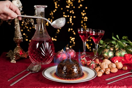 christmas pudding: Hand serving burning brandy over a christmas or plum pudding