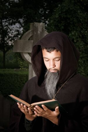 Dark scene of a sinister monk praying in a graveyard photo