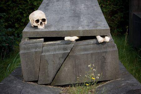 Halloween scene of broken bones and skull on a tombstone photo