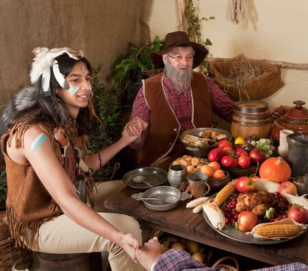 Reenactment scene of the first Thanksgiving Dinner in Plymouth in 1621 with a Pilgrim family and a Wampanoag Indian Stock Photo - 7795404