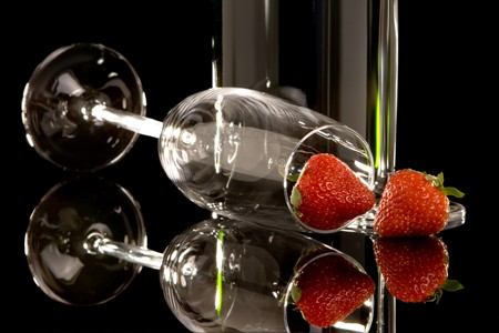 Fresh strawberries and champagne glasses reflected on black photo