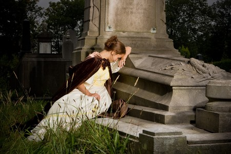 cry: Young woman in victorian dress mourning on a tomb