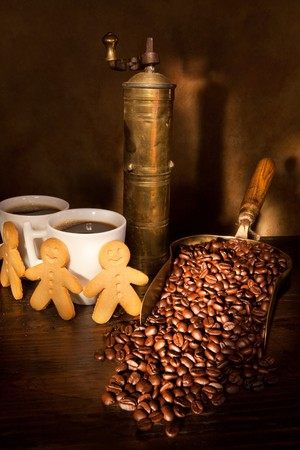 Antique coffee grinder with steaming coffee, cookies and books photo