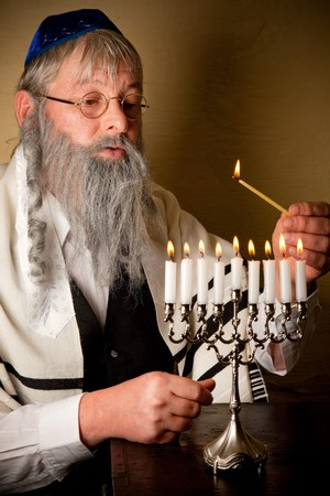 Old jewish man with beard lighting the candles of a menorah photo