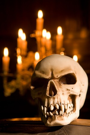 Freaky skull on a coffin lit by candles photo